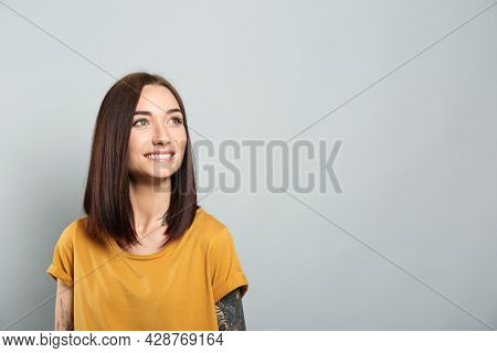 Portrait Of Pretty Young Woman With Gorgeous Chestnut Hair And Charming Smile On Light Grey Backgrou