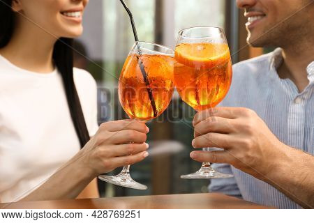 Couple Clinking Glasses Of Aperol Spritz Cocktails Outdoors, Closeup