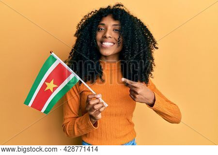 African american woman with afro hair holding suriname flag smiling happy pointing with hand and finger