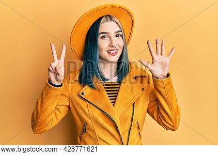 Young modern girl wearing yellow hat and leather jacket showing and pointing up with fingers number seven while smiling confident and happy.