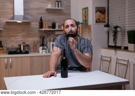 Pensive Man Drinking Glass Of Wine While Sitting Alone And Depressed. Person With Alcohol Addiction