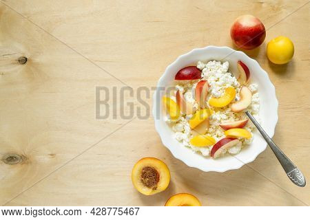 Cottage Cheese With Nectarine In White Bowl On Wooden Background. Space For Text