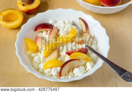 Cottage Cheese With Nectarine In White Bowl On Wooden Background