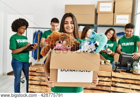 Group of young volunteers working at charity center. Woman smiling happy and holding box with toys to donate.