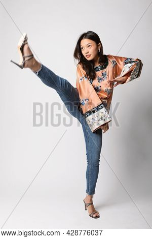 Young Asian girl with a traditional Chinese shirt makes a kunfu move. Isolated, on white background