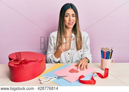 Young hispanic woman making valentine gift sitting on the table pointing aside worried and nervous with forefinger, concerned and surprised expression