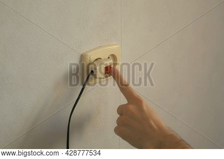 Mans Hand Turns Off The Plug Into An Outlet And Puts On The Red Button. Electric Extension Cable Wit
