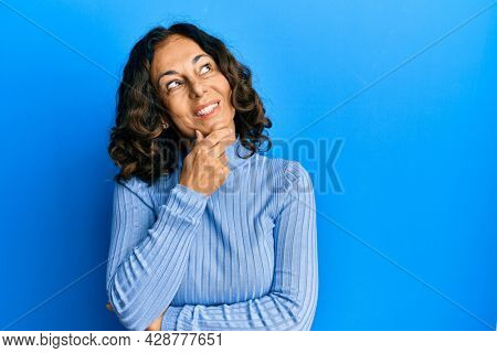 Middle age hispanic woman wearing casual clothes with hand on chin thinking about question, pensive expression. smiling with thoughtful face. doubt concept.