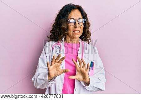 Middle age hispanic woman wearing doctor uniform and glasses disgusted expression, displeased and fearful doing disgust face because aversion reaction. with hands raised
