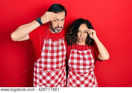 Middle age couple of hispanic woman and man wearing cook apron worried and stressed about a problem with hand on forehead, nervous and anxious for crisis