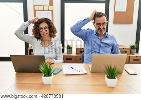 Middle age hispanic woman and man sitting with laptop at the office confuse and wonder about question. uncertain with doubt, thinking with hand on head. pensive concept.