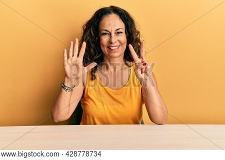 Beautiful middle age woman wearing casual clothes sitting on the table showing and pointing up with fingers number seven while smiling confident and happy.