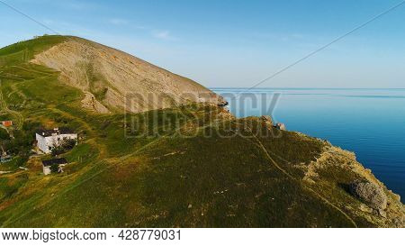 Top View Of Rocky Cape On Background Of Blue Sea. Shot. Remote Life In House On Sea Cape. Beautiful