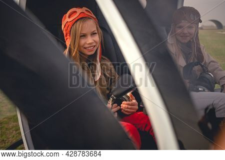 Smiling Tween Girl Sitting In Cockpit Of Landed Helicopter Near Friend
