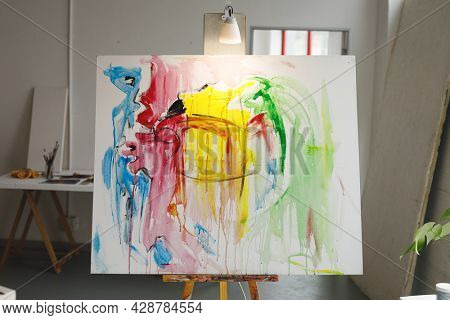 Modern abstract oil painting on canvas sitting on easel in artists studio. creation and inspiration at an artists painting studio.