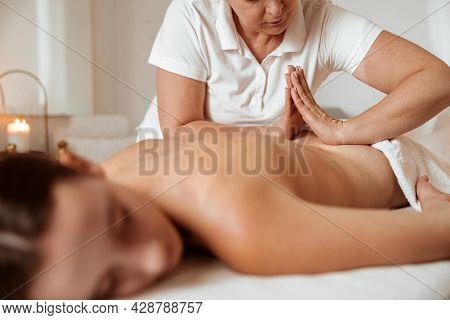 Female Client Receiving Therapeutic Back Massage In Spa Salon