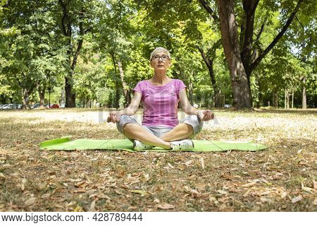 Senior Caucasian Woman Doing Yoga Exercise And Concentrating On Breathing.