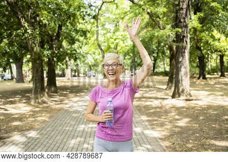 Smiling Senior Caucasian Woman Waving To Her Friend While Jogging In The Park.