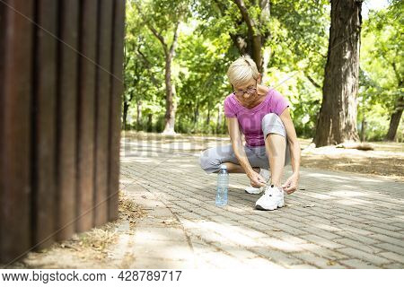 Senior Caucasian Woman Tying Her Shoelace Before Jogging In The Park.