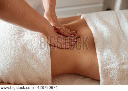 Masseuse Massaging Female Client Abdomen In Spa Salon