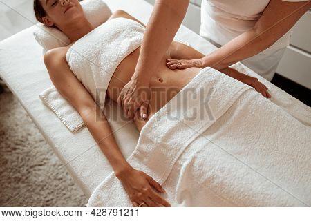 Masseuse Hands Massaging Woman Abdomen In Spa Salon