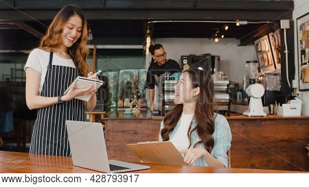 Cheerful Asian Lady Waitress With Notebook Taking Receive Order Menu From Young Client Girl At Urban