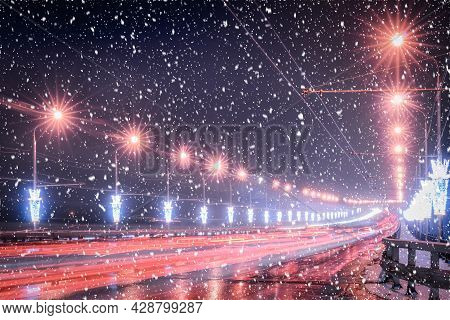 Traces Of Headlights From Cars Moving At Winter Night On The Bridge In A Snowfall. Lights Reflecting