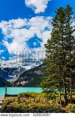 The lake embankment with green lawns and flower beds. Sunny fine day. Glacial Lake Louise in Banff  Park in Canada, Canadian Rockies. The concept of ecological and photo tourism