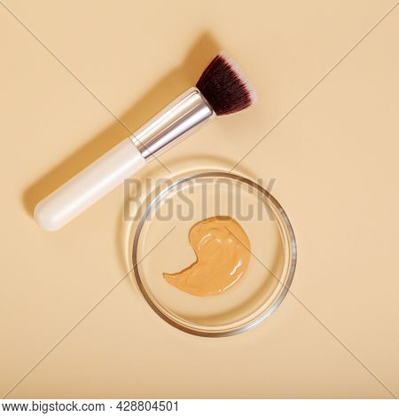 Foundation Swatch And Makeup Brush On Color Beige Background. Swatch Tonal Base In Petri Dish Labora