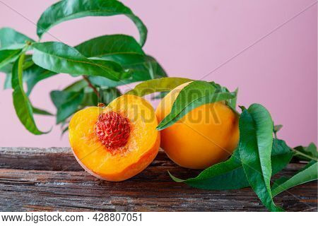 Peaches With Leaves On Wooden Board. Peach In Halves With Bone. Ripe Juicy Peaches. Fresh Organic Pe