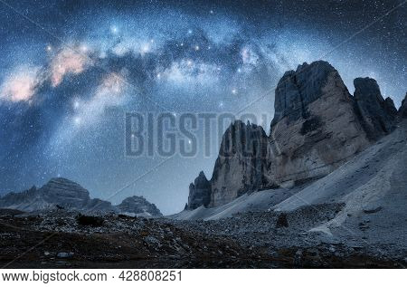 Milky Way Arch And Mountain Peaks At Night In Summer. Beautiful Landscape With Blue Sky With Arched