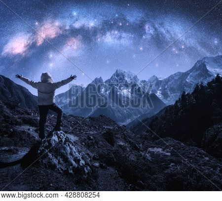 Arched Milky Way, Sporty Man On The Stone And Mountains In Snow At Starry Night. Happy Young Man, Sk