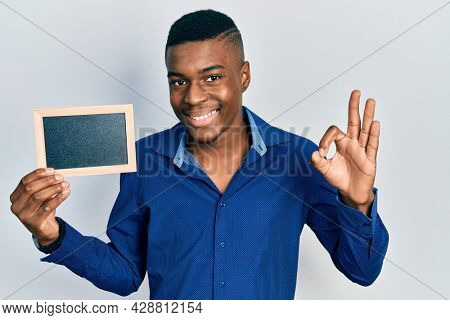 Young african american man holding empty frame doing ok sign with fingers, smiling friendly gesturing excellent symbol