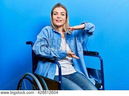 Beautiful caucasian woman sitting on wheelchair gesturing with hands showing big and large size sign, measure symbol. smiling looking at the camera. measuring concept.