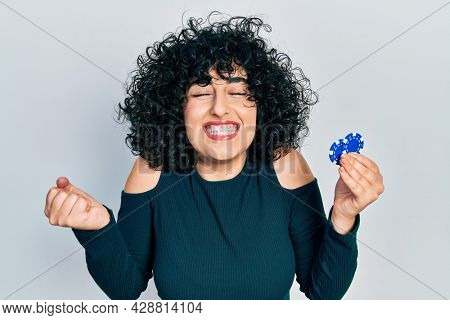 Young middle east woman playing poker holding casino chips screaming proud, celebrating victory and success very excited with raised arm