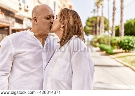 Middle age hispanic couple of husband and wife together on a sunny day outdoors. Kissing in love at the city
