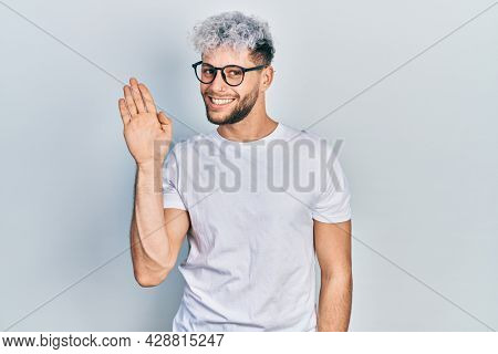 Young hispanic man with modern dyed hair wearing white t shirt and glasses waiving saying hello happy and smiling, friendly welcome gesture