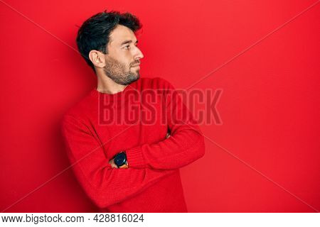 Handsome man with beard wearing casual red sweater looking to the side with arms crossed convinced and confident