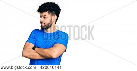 Young arab man with beard wearing casual blue t shirt looking to the side with arms crossed convinced and confident