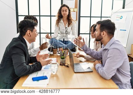 Businesswoman enjoys meditating during meeting. Sitting on desk near arguing partners at the office.