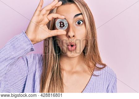 Beautiful hispanic woman holding virtual currency bitcoin scared and amazed with open mouth for surprise, disbelief face