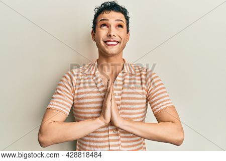 Handsome man wearing make up wearing casual t shirt begging and praying with hands together with hope expression on face very emotional and worried. begging.