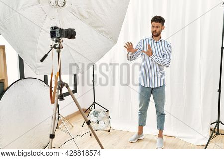 Arab young man posing as model at photography studio disgusted expression, displeased and fearful doing disgust face because aversion reaction.