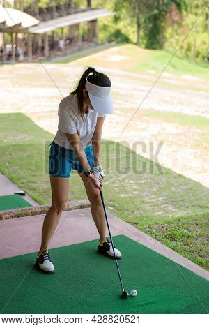 Asian Golfer Woman Swing Golf Ball Practice At Golf Driving Range For Relax And Healthy Care Port. L