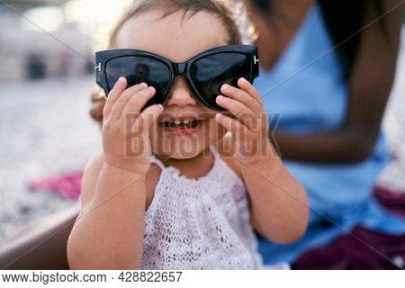 Enthusiastic Little Girl Holding Big Sunglasses With Her Hands