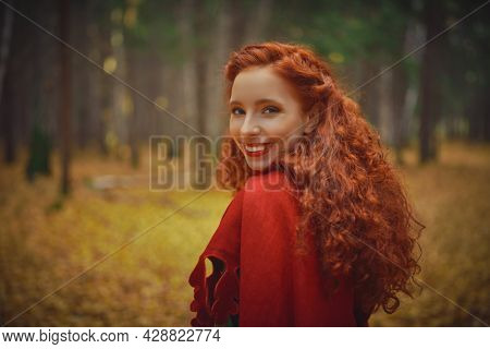 Happy beautiful red haired girl in a traditional green celtic dress and a red cloak is in forest. Historical reconstruction of ancient Celtic times.