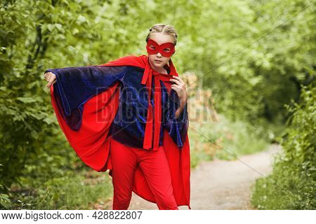 A blonde girl in a superhero costume and mask emotionally poses on lawn against the background of a summer forest in the open air. Sunny summer days. Summer holidays. Games in the park.