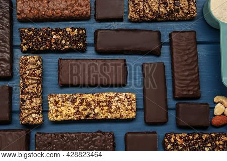 Different Tasty Bars, Nuts And Scoop Of Protein Powder On Blue Wooden Table, Flat Lay