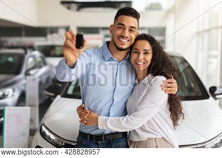 Happy Middle-eastern Family Buying New Car In Luxury Showroom