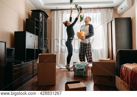 Moving Day, Move Into New Home. Young Happy Couple, Newlyweds Family Having Fun In Room With Housepl